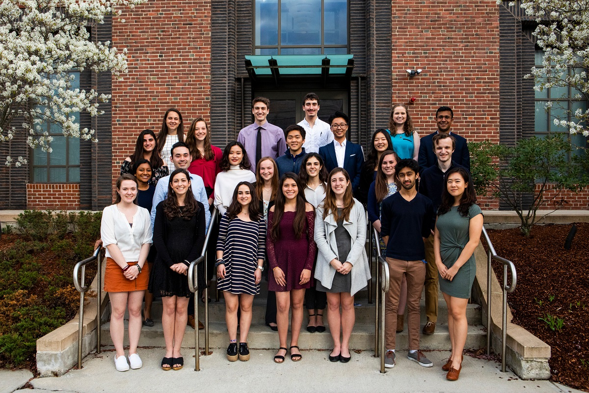 Student scholars in cohort two pose on steps outside of a brick building.