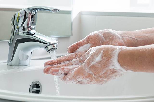 Person washes hands with soap.