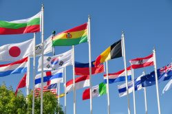 various flags of the world blowing in the breeze against a blue sky.